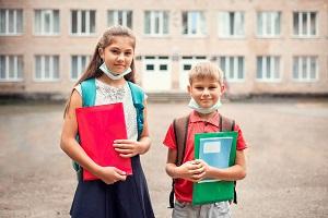 dzieci w maseczkach przed szkola
