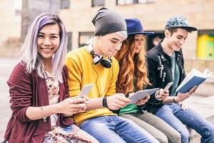 usmiechnieci nastolatkowie z tabletami i smartfonami