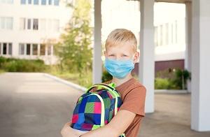 chlopiec w masecke stoi przed szkola z plecakiem