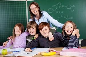 usmiechnieta nauczycielka z grupa uczniow