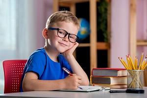 usmiechniety chlopiec siedzi przy biurku i odrabia lekcje