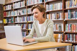 nauczycielka korzystajaca z laptopa w bibliotece