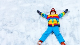 chlopiec robi orzelka na sniegu