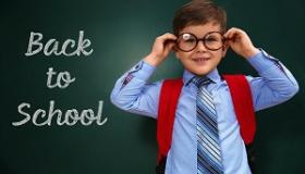 chlopiec przy tablicy z napisem powrot do szkoly