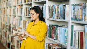 kobieta czyta ksiazke w bibliotece