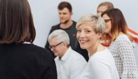 usmiechnieta kobieta patrzy w obiektyw podczas spotkania