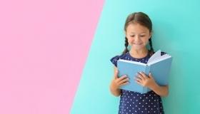 dziewczynka czyta ksiazke na tle pastelowych kolorow