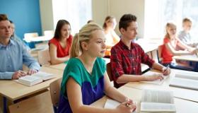 uczniowie siedza w ławkach w sali lekcyjnej