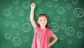 dziewczynka na tle tablicy zapisanej ikonkami usmiechnietych buziek