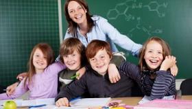 usmiechnieta nauczycielka obejmuje grupe uczniow w klasie