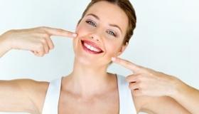 kobieta wskazuje na swoj usmiech