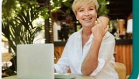 usmiechnieta kobieta przy biurku z laptopem
