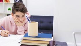 chlopiec odrabia lekcje przy biurku z ksiazkami
