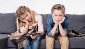 znudzone dzieci siedza na kanapie