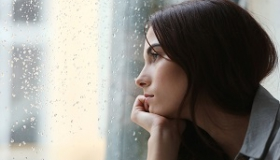 zadumana kobieta wyglada przez zalana deszczem szybe