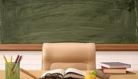 biurko nauczyciela na tle tablicy w klasie szkolnej