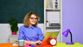 nauczycielka przy biurku z laptopem i budzikiem
