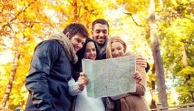 grupa przyjaciol studiuje mape na tle jesiennych drzew